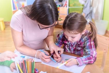 Kindergarten Teacher Supporting Child in Creative Activities